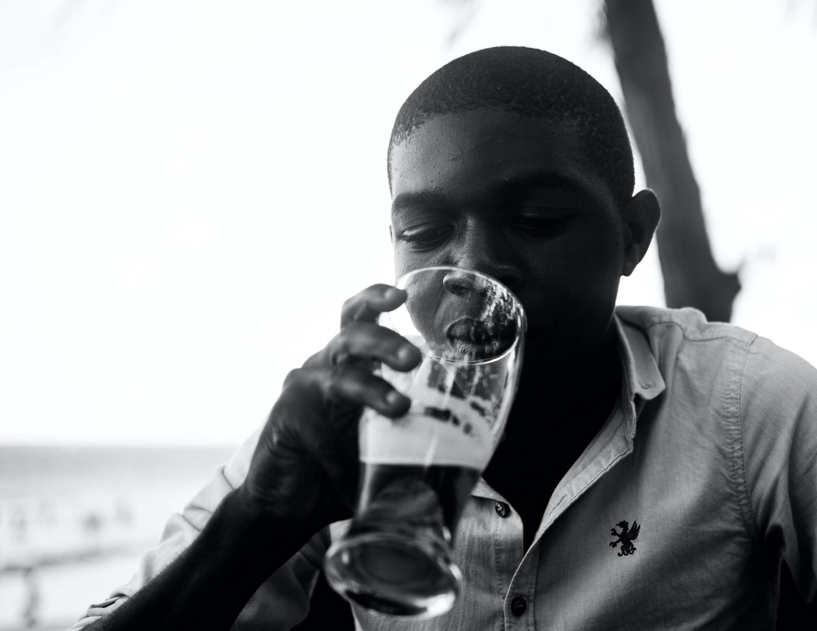 a man looks down into an almost empty glass of beer